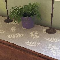 Table runner in Natural Rustic linen with off white handprinted leaf pattern....