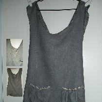 A gray linen criss-cross tunic apron, trimmed with contrasting gray and white bias tape and two ...
