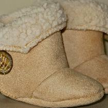 Cozy infant booties made of faux suede/sheepskin fabric with Velcro closures...